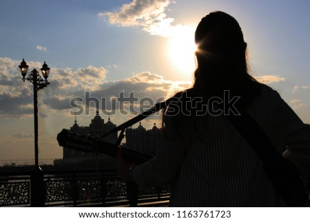 the guitarist on a sky background , the guitarist in the sun