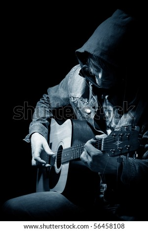 The guitarist plays an acoustic guitar