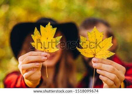 The guy and the girl are holding maple leaves in their hands. couple covers their faces with yellow maple leaves. Stylishly dressed guy and girl. The guy and the girl in red jackets in yellow forest.