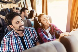 The guy and the girl are on the bus. The girl has headphones. He and the guy are discussing something and smiling. Behind them sit other tourists who are looking out the window to the sights.