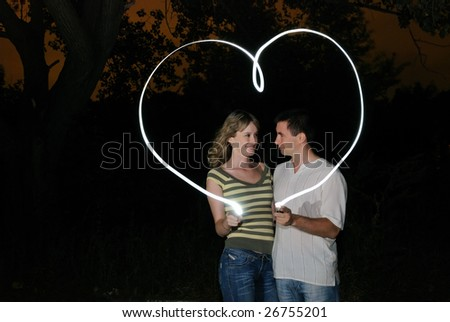The guy and the girl draw heart a finger. Isolate on black