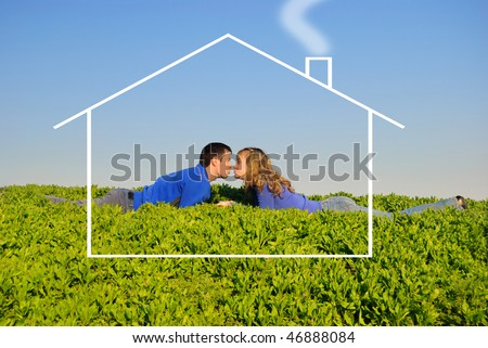 The guy and the girl lay in a grass and kisses