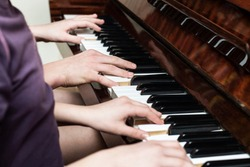 The guy and the girl play both on the piano in four hands, close up, they are getting ready to perform at the concert, their hands are playing a famous tune