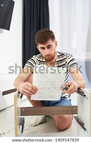 the guy assembles furniture according to the instructions