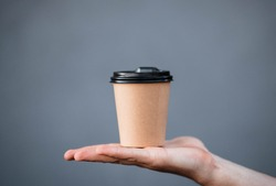 The guy holds a paper cup with coffee or tea. Have a cup of coffee. Disposable paper cup. Beautiful girl with blond hair. Casual style, white shirt and jeans. Take it away. Hot drink. Empty space.