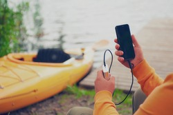 The guy holds a portable charger with a smartphone in his hand. A man against the background of water and a kayak charges the telephone with Power Bank. Concept on the theme of tourism