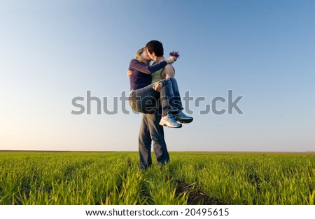The guy holds the girl on hands and kisses
