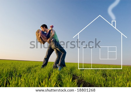 The guy holds the girl on hands, kisses and dreams about the new house