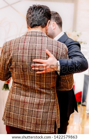 The guy hugs the guy and wishes him a successful wedding.
