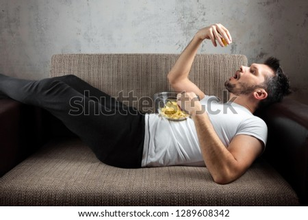 The guy in the shirt is lying on the couch, eating chips and watching a sports channel. The concept of laziness, frustration, procrastination, the person at home. #1289608342