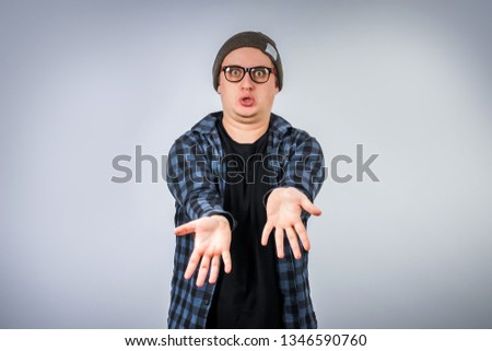 The guy is emotionally outraged or something to ask her. Hipster in a hat and a plaid shirt. Emotional portrait. Negative emotion. Gray background. #1346590760