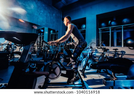 The guy is engaged in a bicycle simulator in the gym. Toned image. The guy is exercising on a stationary bike #1040116918