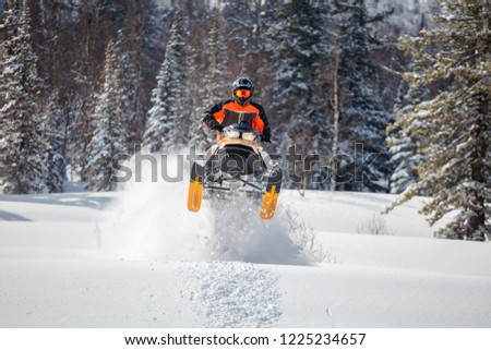 the guy is flying and jumping on a snowmobile on a background of winter forest  leaving a trail of splashes of white snow. bright snowmobile and suit without brands. extra high quality Сток-фото ©
