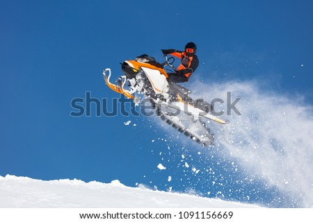 the guy is flying on a snowmobile on a background of blue sky leaving a trail of splashes of white snow. bright snowmobile and suit without brands. Сток-фото ©