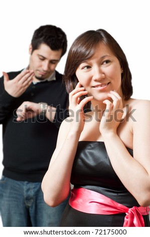 The guy is getting impatient and mad while his girlfriend is on the phone