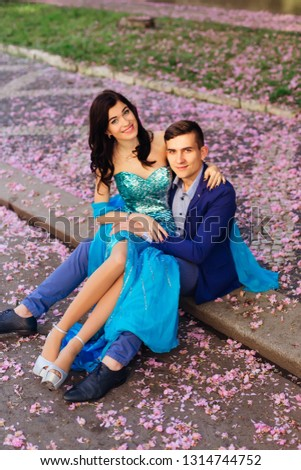 The guy is sitting on the sidewalk and the girl sits on his knees among the petals of flowers. they smile and look at the camera lens #1314744752