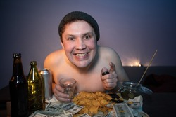 The guy is smiling at the camera and there is beer and chips on the table