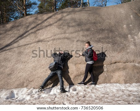 The guy is standing with his hands on the back of his neck and facing the big stone, and the girl is looking at it - Shutterstock ID 736520506