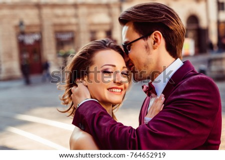 The guy kisses a beautiful girl in the beautiful sunny morning of the ancient city #764652919