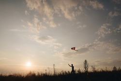 The guy runs with a kite on the hill. Silhouette of a man at sunset. Beautiful nature.