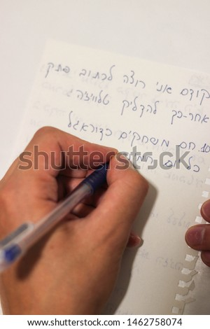 The guy's hand writes a sentence in Hebrew. Translation: First I want to write a note. Then turn on the TV. 10. You play football every Thursday