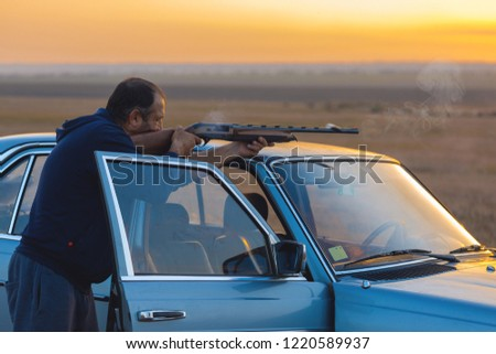 The guy shoots cartridges with a gun in nature, The hunter shoots at the target at sunset #1220589937