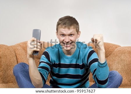the guy shouts happily, watching tv, sitting on the couch