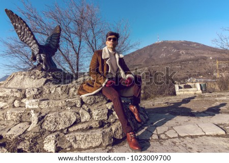 The guy sits on a stone at the monument to the Eagle against the backdrop of the city of Pyatigorsk