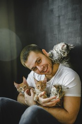 the guy sits on the floor leaning against the wall among the maine coon cats. male cat lover playing with cats sitting on the floor. incredible beautiful cats and model in T-shirt