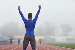 The guy the athlete raised his hands up at the stadium in the fog.
