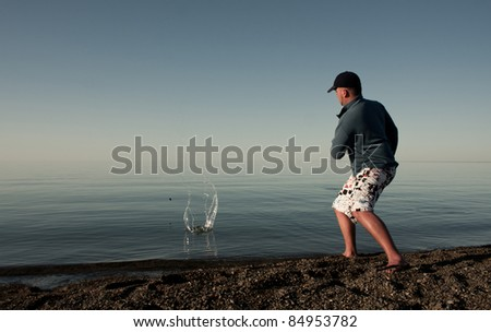 The guy throws stones in water