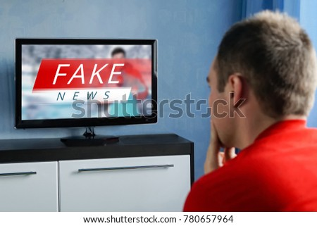 The guy watching the fake news on TV. Corrupt journalism. The false reporting. Deception, propaganda and misinformation from television. brainwashed brains of men watching TV. Сток-фото ©