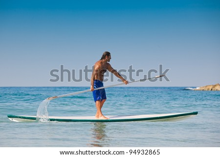 The guy with an oar on a surfboard (Stand Up Paddling). The beautiful brawny guy with an oar in hands on a surfboard.
