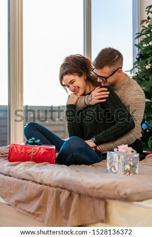 The guy with the girl celebrate the new year. Young couple celebrates christmas. #1528136372