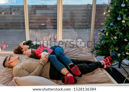 The guy with the girl celebrate the new year. Young couple celebrates christmas. #1528136384