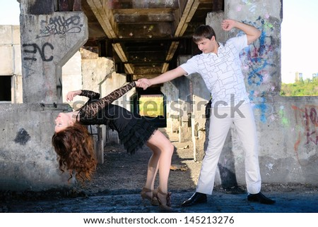 The guy with the girl dance a tango in abandoned room