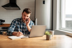 The guy works from home. He sits in the kitchen at the table and uses a laptop computer and speaks on the phone. He is positive, his business is going well.