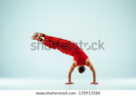 The gymnastic acrobatic caucasian man posing in balance posture on gray studio background