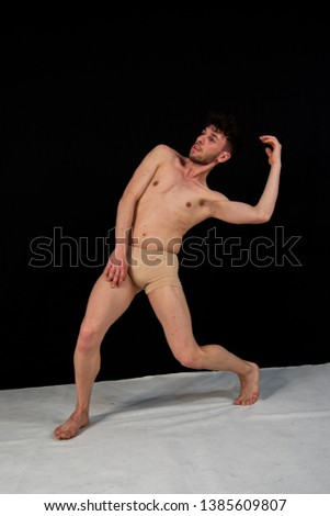The gymnastic pose of the Caucasian man dances in the studio with plastic hand and leg positions. The attractive young man shows modern dance poses, on a black background.