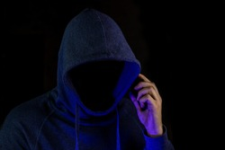 The hacker is calling.  A fraudster is holding a telephone in his hand.