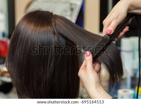The hairdresser does aligns the hair with hair iron to a young girl, brunette in a beauty salon. Professional Hair Care #695164513