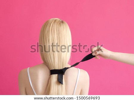 The hairstyle Beauty concept Woman's hand is untying the black ribbon on the hair of the blonde woman on a pink background