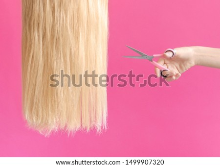 The hairstyle Concept photo for hairdresser's shop The girl is going to cut off a strand of long blond hair with scissors on a pink backdrop