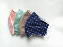 The half folded cloth face masks double layered which can be washed and reused many times for wearing to protect against Covid-19 virus or Corona virus and PM2.5 dust when out in public, new normal.