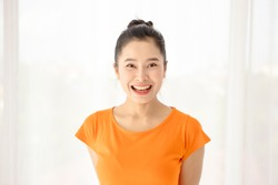 The half length shot of a beautiful face Asian woman with a black hair bun, smiling at the camera happily. A simple female portrait shot with natural light. Showing positive and friendly gestures.