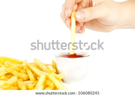 The hand dips a potato in ketchup