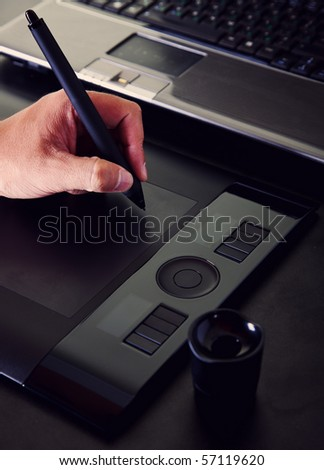 The hand draws a pen on a working surface of a tablet