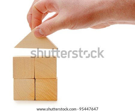 The hand establishes a toy roof on wooden cubes. Isolated on white
