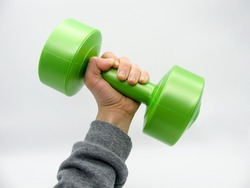 The hand holds a green plastic fitness dumbbell weighing two kilograms. Training with dumbbells.