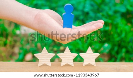 The hand holds a human figure and three stars. The concept of a business leader and a skilled manager. Success and achievement. Increase of efficiency of work and qualification of personnel. #1190343967